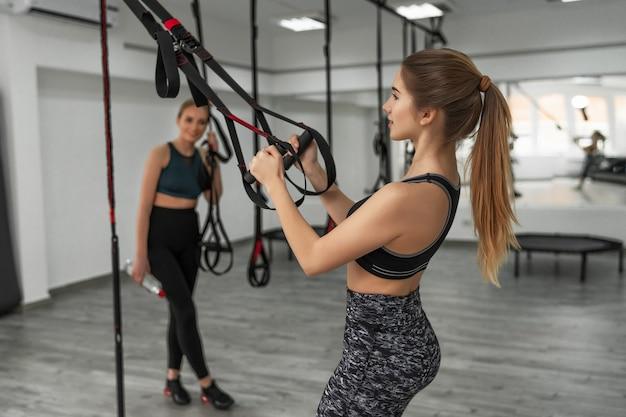 스포츠 사람들이 trx로 야외에서 훈련하고 있습니다.