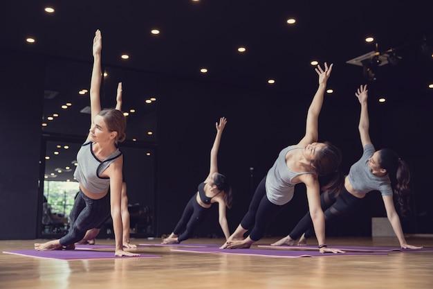 Группа спортивных смешанных гонок кавказских и азиатских людей, практикующих йогу как женщин, так и мужчин, представляют в спортзале студии, йога и фитнес работают над концепцией здравоохранения