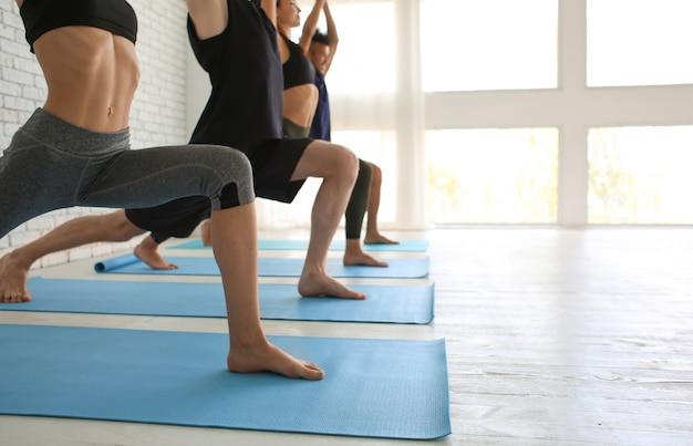 Группа спортивных людей, практикующих йогу в помещении