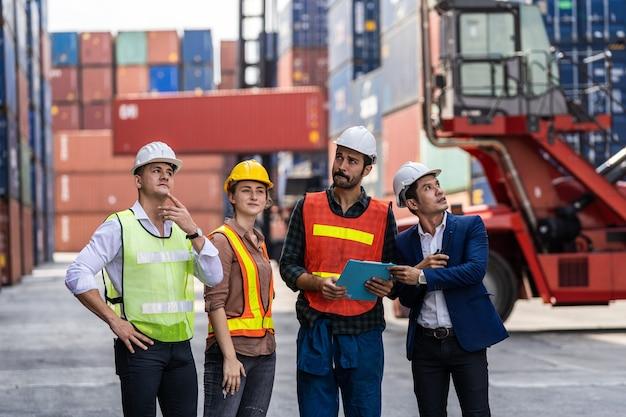Группа штатных работников, стоящих и проверяющих коробку контейнеров с грузового судна для экспорта и импорта