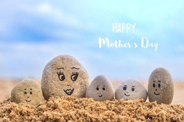 砂に描かれた顔を持つ石のグループ。母と彼女の子供たち。幸せな母の日のコンセプトカード。