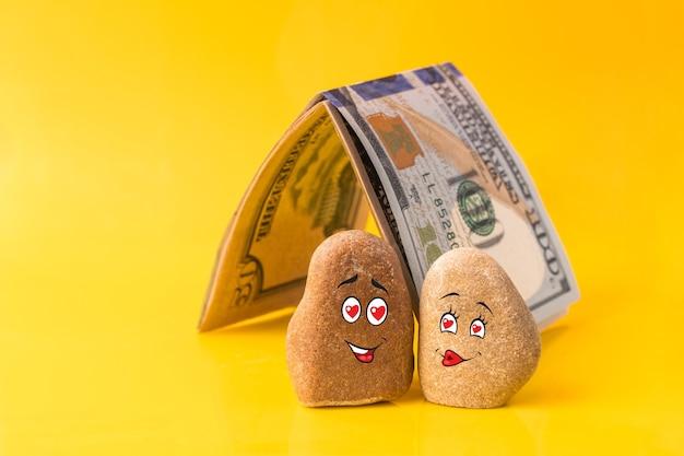 재미있는 얼굴이 그려진 돌과 돈으로 만든 집. 연인의 커플은 좋은 재정 계획을 가지고 있습니다. 투자, 은행 예금, 돈 관리 개념.
