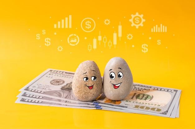재미있는 얼굴과 미국 달러 지폐가 그려진 돌 그룹. 연인의 커플은 좋은 재정 계획을 가지고 있습니다. 투자, 은행 예금, 돈 관리 개념.