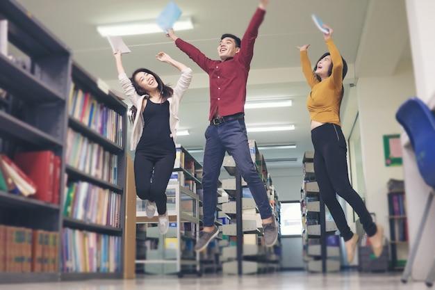 図書館でジャンプする学生のグループはとても幸せそうです。