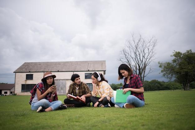 クラス後に公園に座っている学生のグループ。一緒に話を楽しんでください。