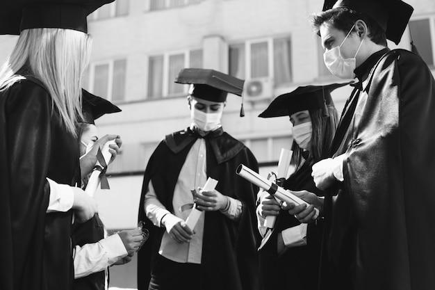 Группа студентов вместе празднует выпускной и в масках для лица