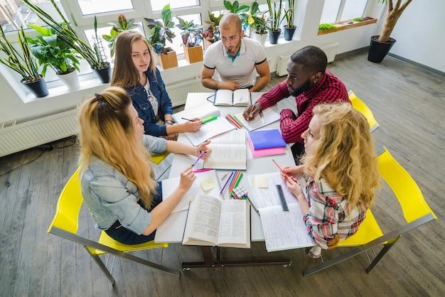 テーブルで協力している学生グループ