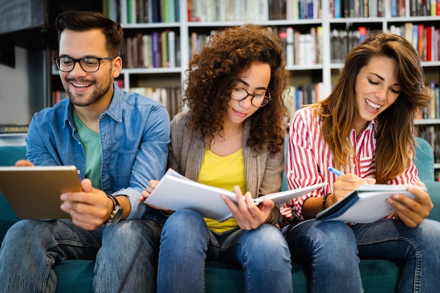 Группа друзей студентов учится в библиотеке. обучение и подготовка к университетскому экзамену.