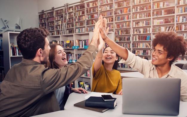 학생 그룹이 도서관에서 하이 파이브를합니다.