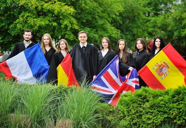 Группа студентов-выпускников факультета иностранных языков в халатах держат в руках флаги великобритании, франции, испании и германии.