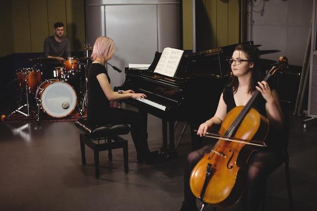コントラバス、ドラムセット、ピアノを演奏する学生のグループ