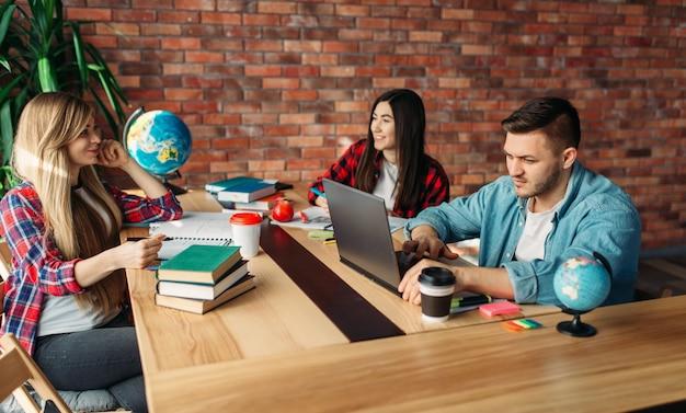 Группа студентов, обучающихся за столом вместе. люди с ноутбуком просматривают информацию в интернете