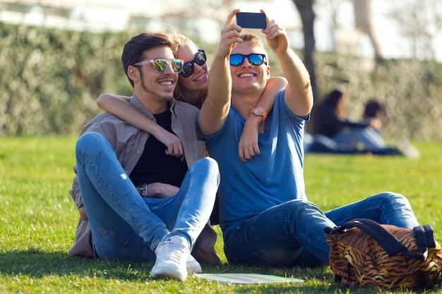 Группа студентов фотографирует с помощью смартфона на улице.