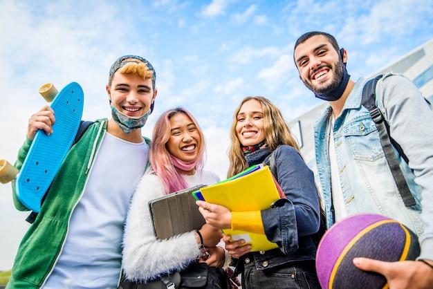 Группа студентов в защитной маске улыбается и позирует на открытом воздухе