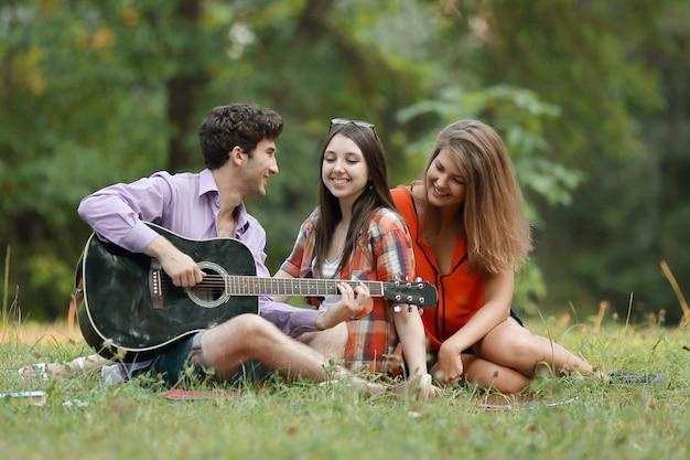 기타를 가진 학생들의 그룹은 잔디에 앉아 휴식을 취