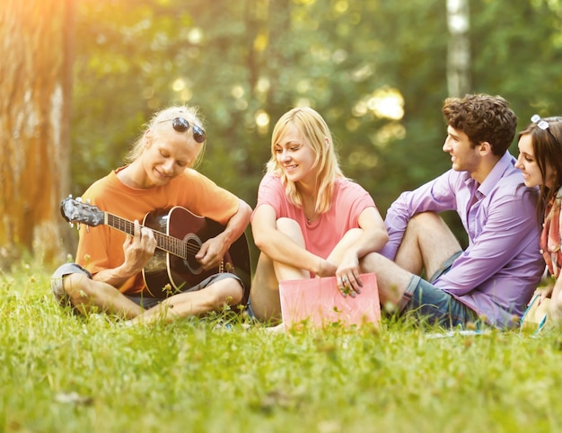 공원에서 쉬고 기타를 가진 학생의 그룹