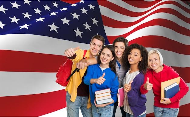 Группа студентов с книгами на фоне американского флага