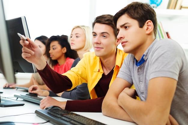 Группа студентов с ноутбуком и книгой делает уроки