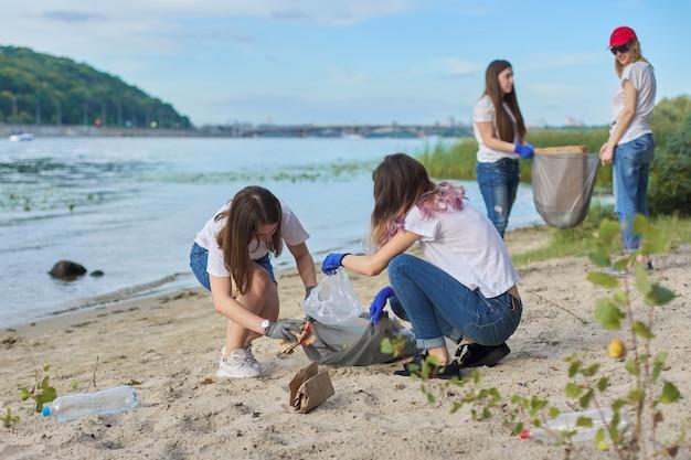 プラスチックのゴミの掃除をしている自然界の教師と一緒の学生のグループ。環境保護、若者、ボランティア、チャリティー、エコロジーの概念
