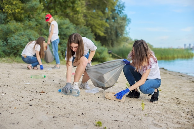 Группа студентов с учителем на природе убирают пластиковый мусор. охрана окружающей среды, молодежь, волонтерство, благотворительность и экология.