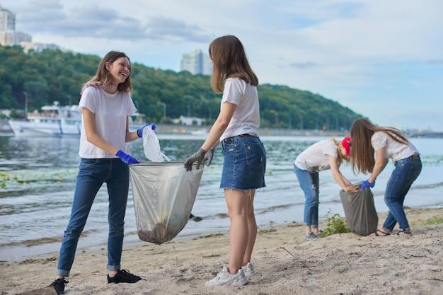 プラスチックごみの掃除をしている自然の中で教師と一緒の学生のグループ。環境保護、若者、ボランティア、チャリティー、エコロジーの概念