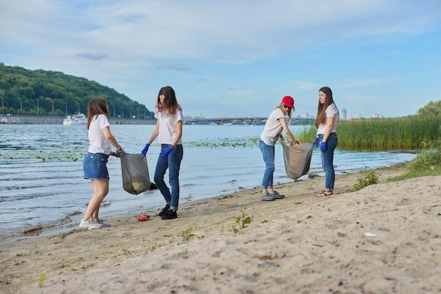 プラスチックごみの掃除をしている自然の中で教師と一緒の学生のグループ