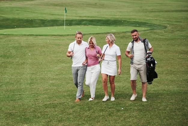 골프 코스에서 세련된 친구 그룹은 새로운 게임을 배우십시오. 경기가 끝난 후 팀은 쉬게됩니다