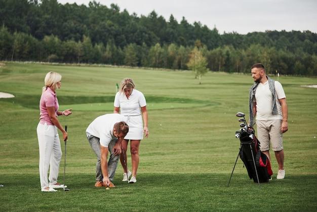 골프 코스에서 세련된 친구들의 그룹은 새로운 게임을 배울 수