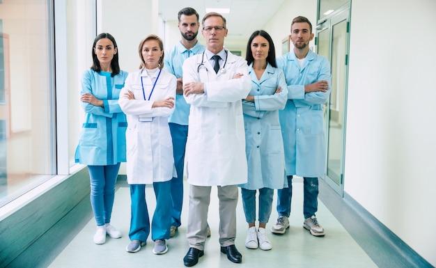 Группа успешных и уверенных в себе современных врачей позируют и смотрят в камеру в коридоре больницы