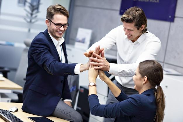 近代的なオフィスで声援を送る、成功したビジネスマンのグループ