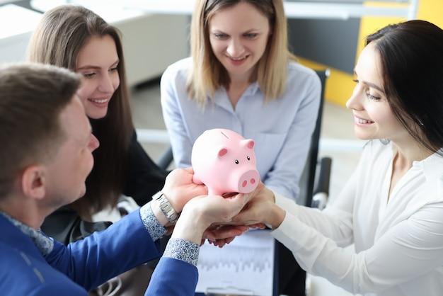 Группа успешных деловых людей, держа в руках розовую копилку крупным планом