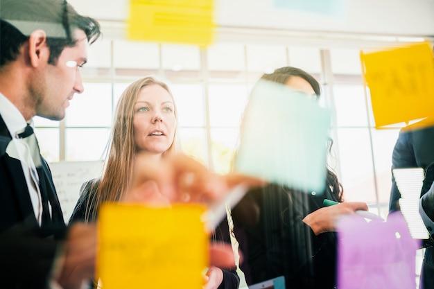 成功したビジネスチームワークのグループ。新しいアイデアのためにガラスの壁にカラフルな粘着紙のメモとのブレインストーミング会議。アジャイル手法を使用してビジネスを行います。技術系スタートアップオフィスでのブレーンストーミング。