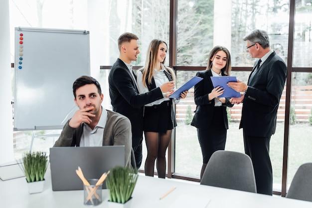Группа успешных бизнесменов, использующих папку перед окнами офисного здания с видом на город.