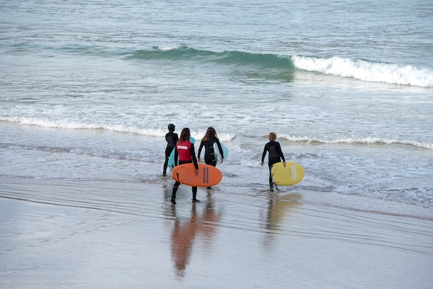 Группа серферов, заходящих в море