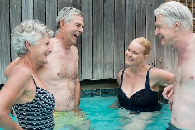 Группа пловцов разговаривает, стоя в бассейне