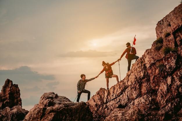 ピーク登山チームワーク旅行トレッキングの勝者の作業を支援するチームの人々のグループ