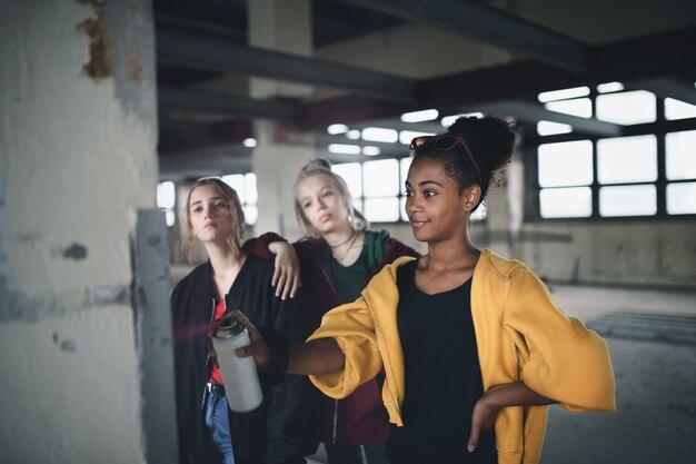 Группа девочек-подростков, стоящая в закрытом помещении в заброшенном здании, используя краску для спрея на стене.