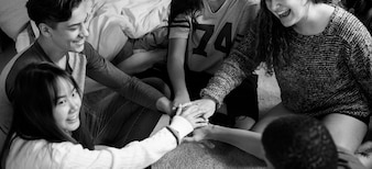 Group of teenagers in a bedroom putting their hands together community and temwork concept