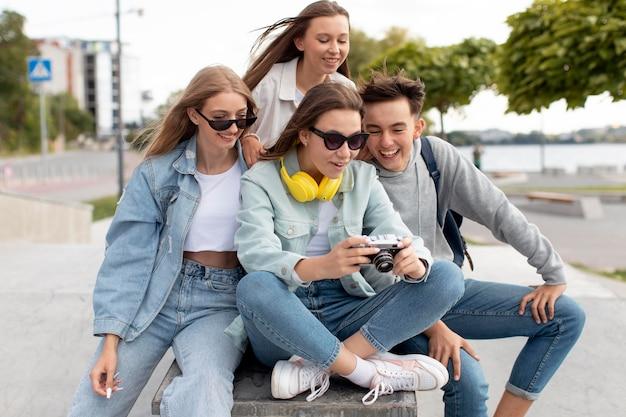 카메라로 사진을 보고 있는 십대 그룹