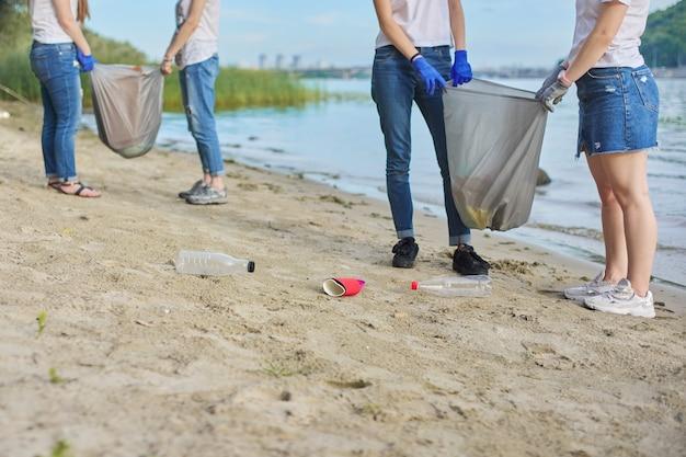Группа подростков на берегу реки собирает пластиковый мусор в мешках. охрана окружающей среды, молодежь, волонтерство, благотворительность и экология.