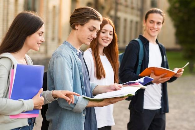 Группа подростков читает заметки проекта
