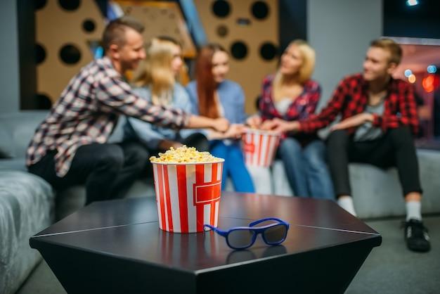 Группа подростков отдыхает на диване в кинозале