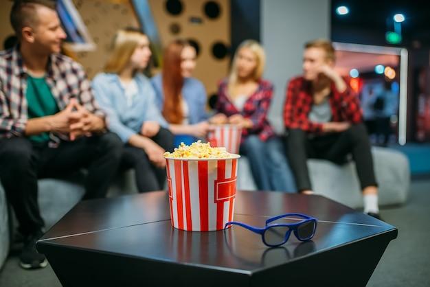 Группа подростков отдыхает на диване и ждет сеанса в кинозале. мужская и женская молодежь, сидя на диване в кинотеатре, попкорн на столе