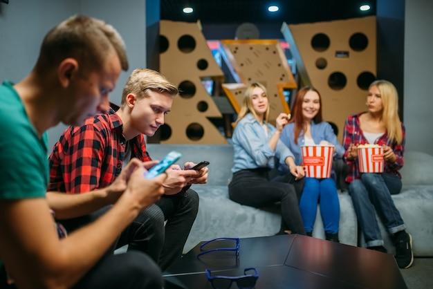 Группа подростков отдыхает на диване и ждет фильма в кинозале. мужская и женская молодежь, сидя на диване в кинотеатре, попкорн на столе