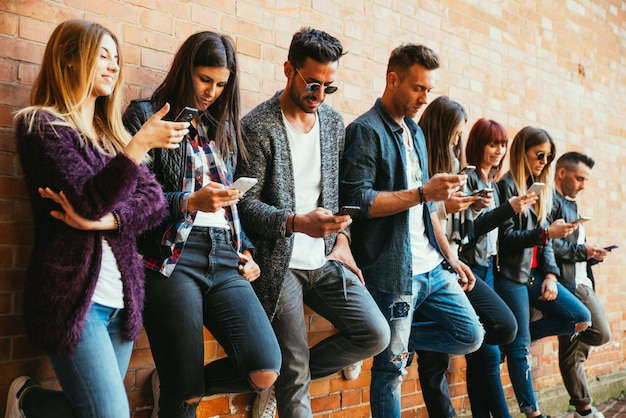 屋外のスマートフォンでティーンエイジャーのグループ