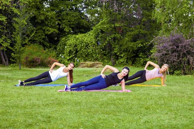 공원의 푸른 잔디에서 운동을 하는 세 명의 아름다운 건강한 칙칙한 여성 그룹, 측면 팔크, 이빨 미소로 카메라를 바라보고 있습니다. 야외 아침, 스포츠 라이프 스타일 웰빙 및 체중 감소.