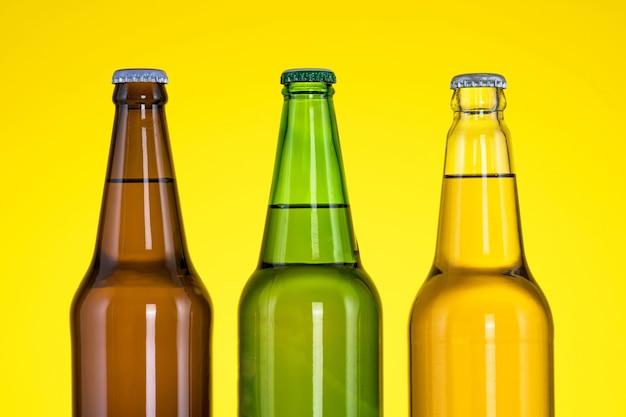 Группа из трех бутылок пива, изолированные на желтом фоне