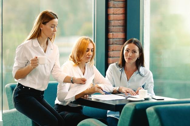 現代のオフィスでビジネスプロジェクトに一緒に取り組んでいる3人の同僚のグループ。若い魅力的な白人女性の笑顔、チームワークの概念。