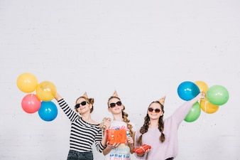 Group of three female friends enjoying the party with presents and balloons