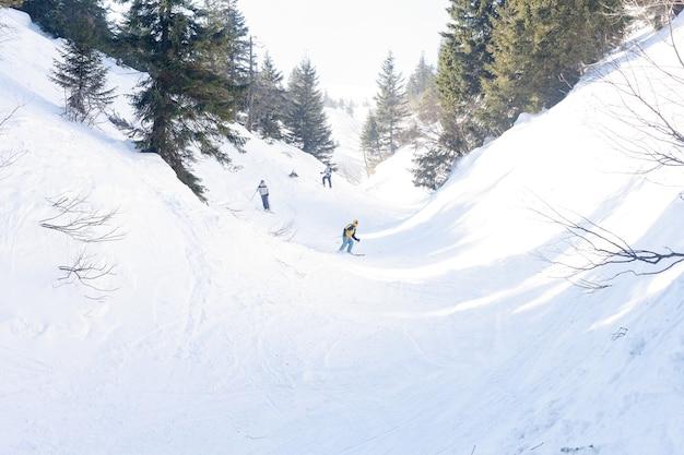 세 명의 프리라이드 스노보더(여성 및 남성)가 눈 슬로프에서 스노우보드 보드를 구르고 타고 아름다운 알프스 산맥을 배경으로 즐길 수 있습니다. 뒷모습.